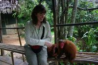Jess grins at an endangered Red-faced Uakari Monkey (Cacajao calvus rubicundus) while simultaneo...